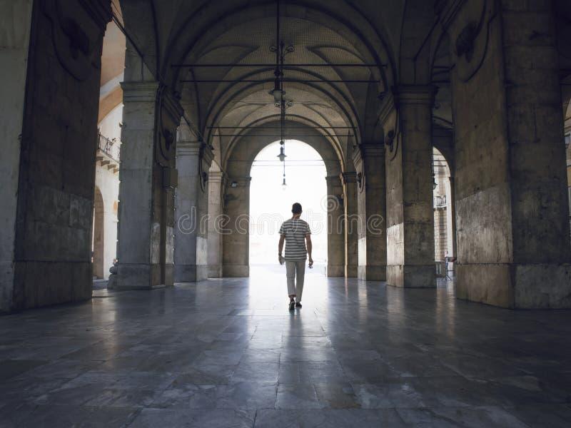 Man som går under tunga valv, i Pisa, Italien Ljust ljust sippra in arkivbild