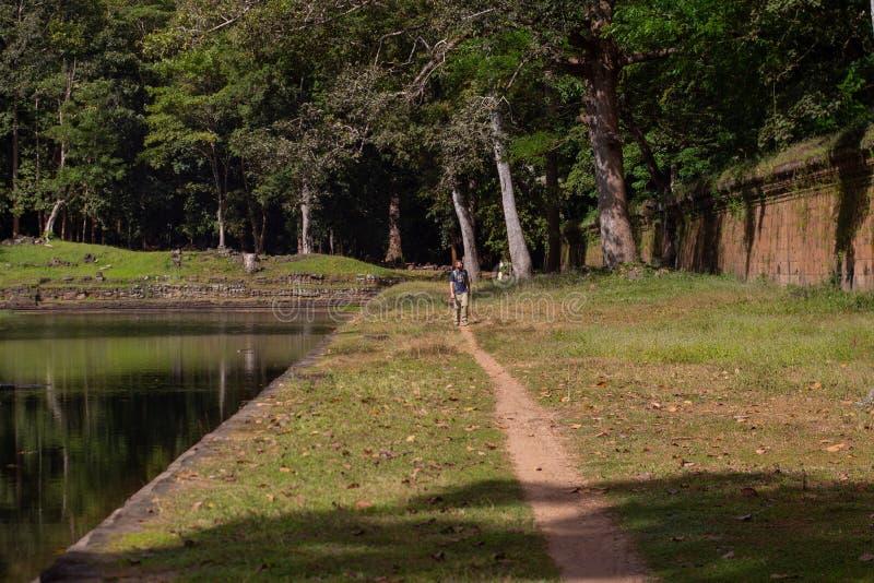 Man som går vid den forntida väggen & pölen i den kambodjanska djungeln av Angkor Thom arkivfoto