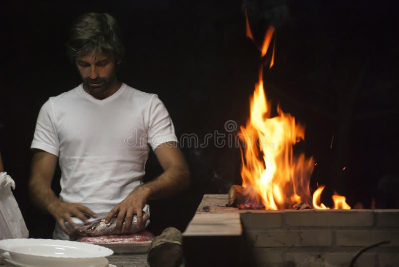 Man som gör en grillfest vid natt arkivfoton