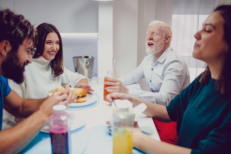 Man som gör hans vänner som skrattar på lunchen royaltyfri fotografi