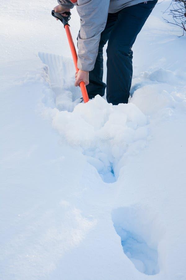 Man som gör klar snö förbi skyffeln efter snöfall utomhus arkivfoton