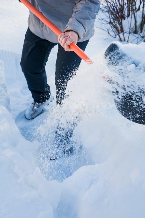 Man som gör klar snö förbi skyffeln efter snöfall utomhus royaltyfri bild
