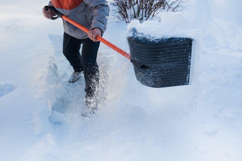 Man som gör klar snö förbi skyffeln efter snöfall utomhus royaltyfria bilder