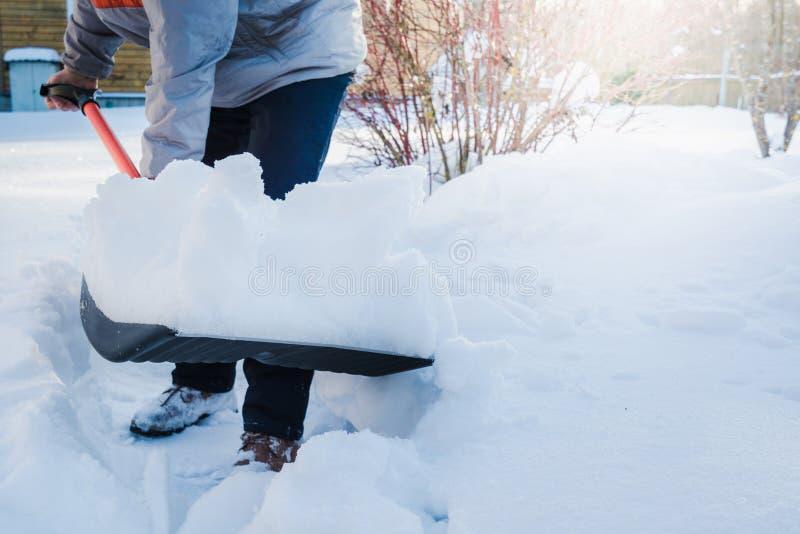 Man som gör klar snö förbi skyffeln efter snöfall utomhus arkivbild