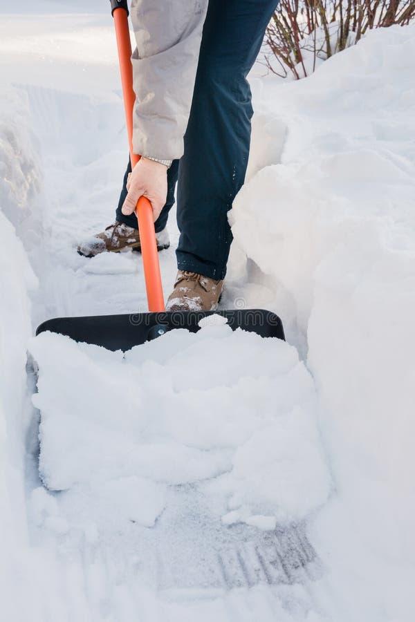 Man som gör klar snö förbi skyffeln efter snöfall utomhus royaltyfri fotografi