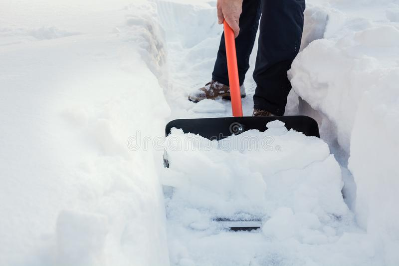 Man som gör klar snö förbi skyffeln efter snöfall utomhus arkivbilder