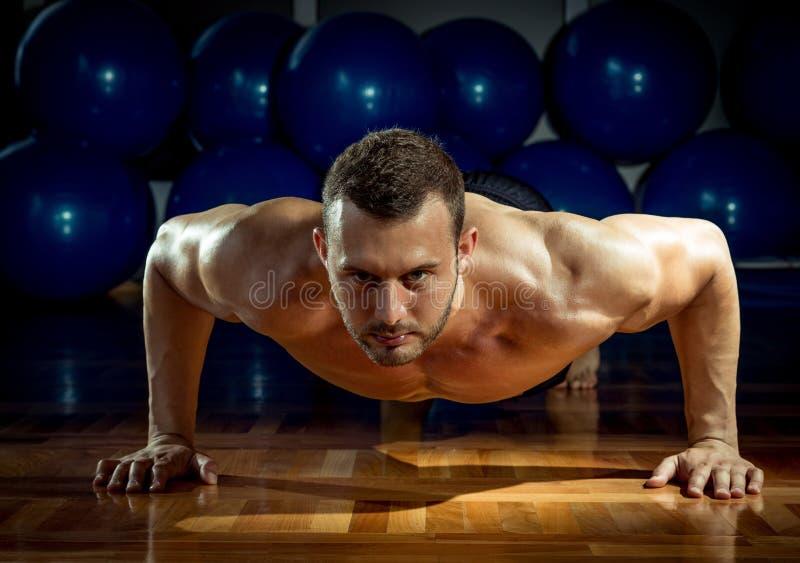 Man som gör push-UPS i idrottshall royaltyfria foton