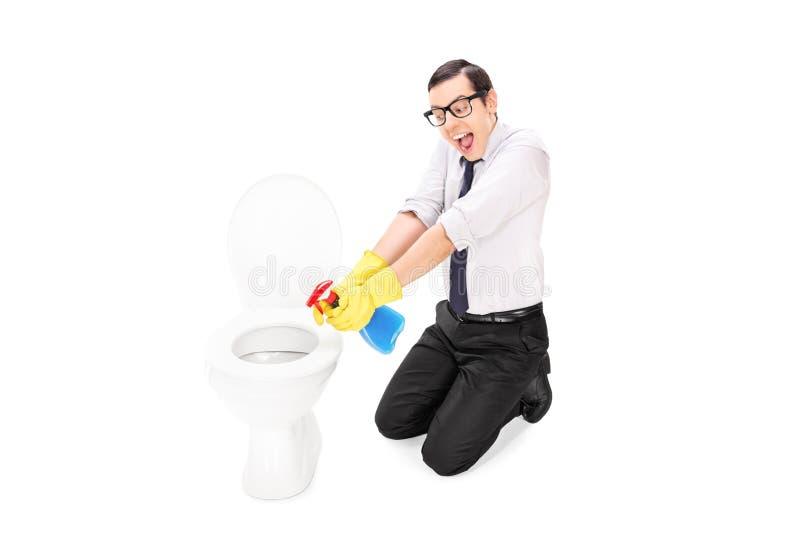 Man som gör ren en toalett med att desinficera sprej royaltyfri foto