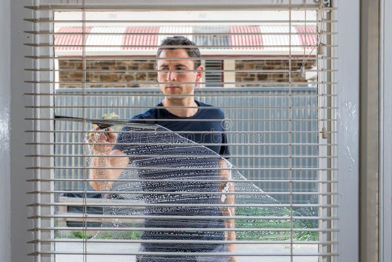 Man som gör ren fönstret av ett hus royaltyfria foton