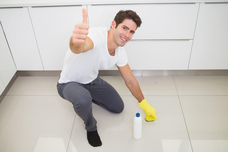 Man som gör ren kökgolvet, medan göra en gest upp tummar royaltyfria foton