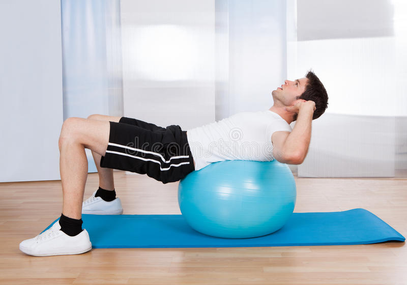 Man som gör Sit Ups On Fitness Ball arkivfoto