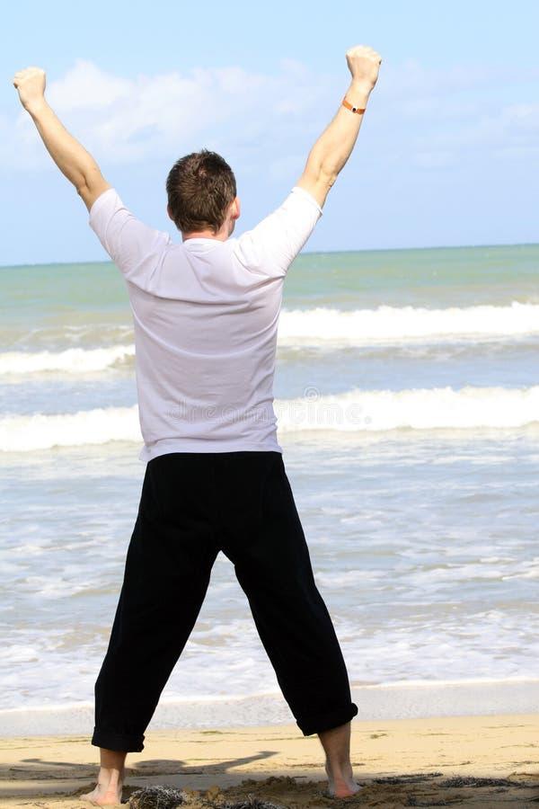 Man som gör sporten på stranden royaltyfri bild
