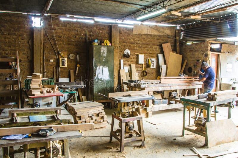 Man som gör träverk i snickeri Snickeriseminarium arkivbild
