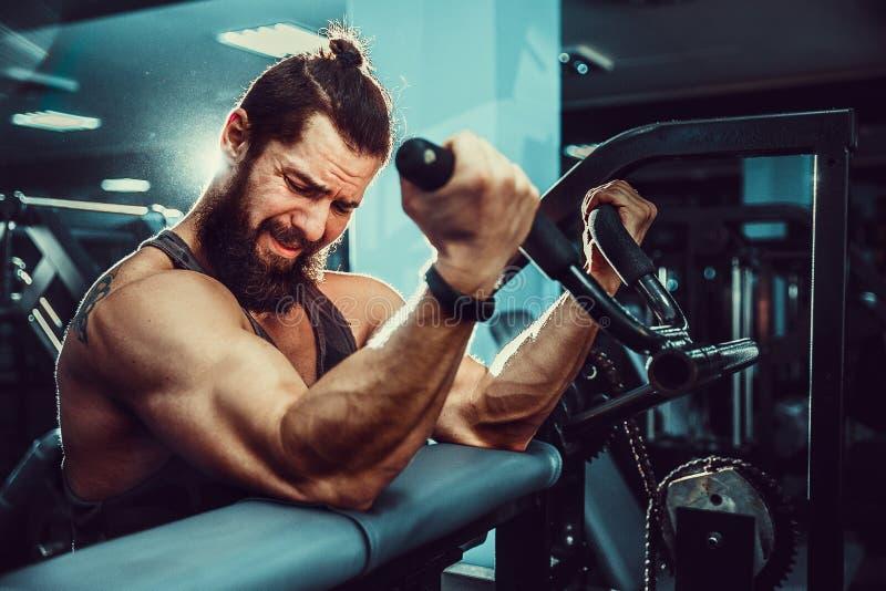 Man som gör tungviktövningen för biceps på maskinen i en idrottshall arkivbilder
