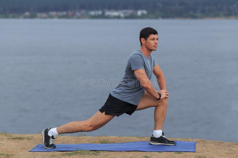 Man som gör utomhus- yoga För yogakondition för ung man som praktiserande övning är utomhus- på det härliga havet Meditation och  royaltyfria bilder