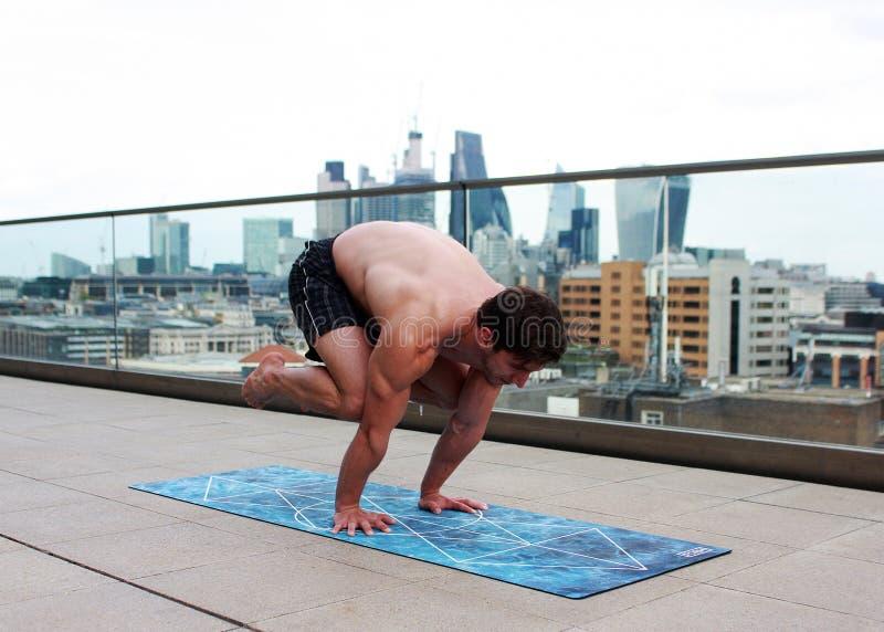 Man som gör yoga på Mat Near Glass Balcony Fence arkivfoton
