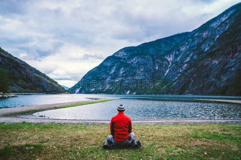 Man som gör yogameditation på mats i molnig morgondet fria nära den härliga sjön Norge Yogameditation i bergman royaltyfri bild