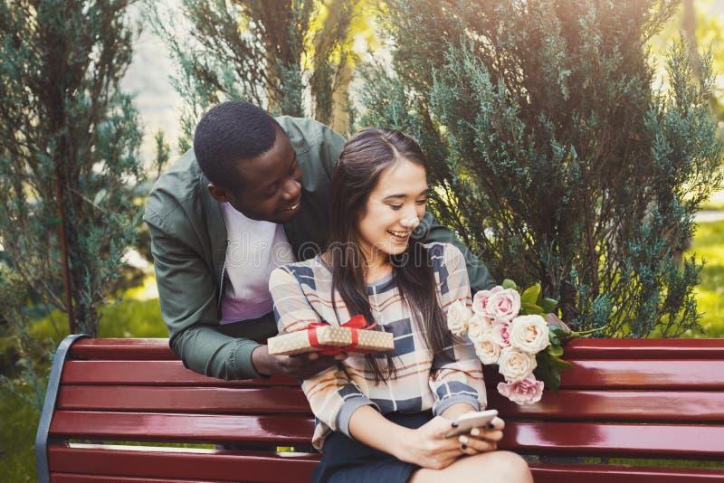 Man som ger blommor och gåvan för hans flickvän fotografering för bildbyråer