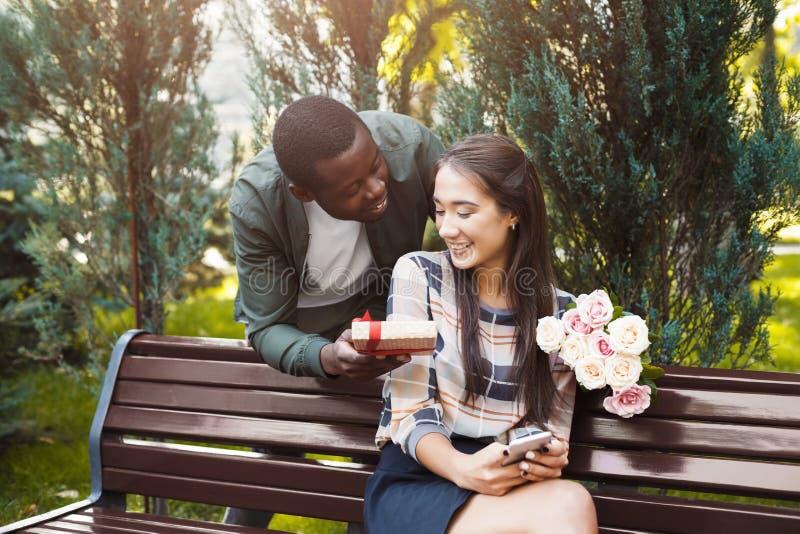 Man som ger blommor och gåvan för hans flickvän arkivfoton