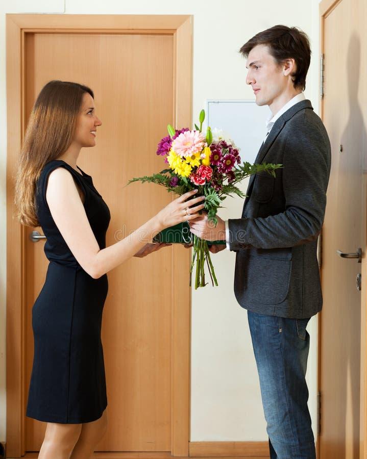 man som ger blommor och gåvan till kvinnan arkivbild