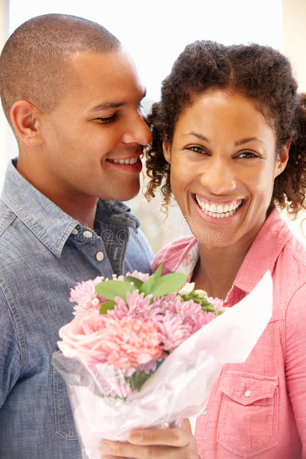 man som ger blommor till kvinnan royaltyfri foto
