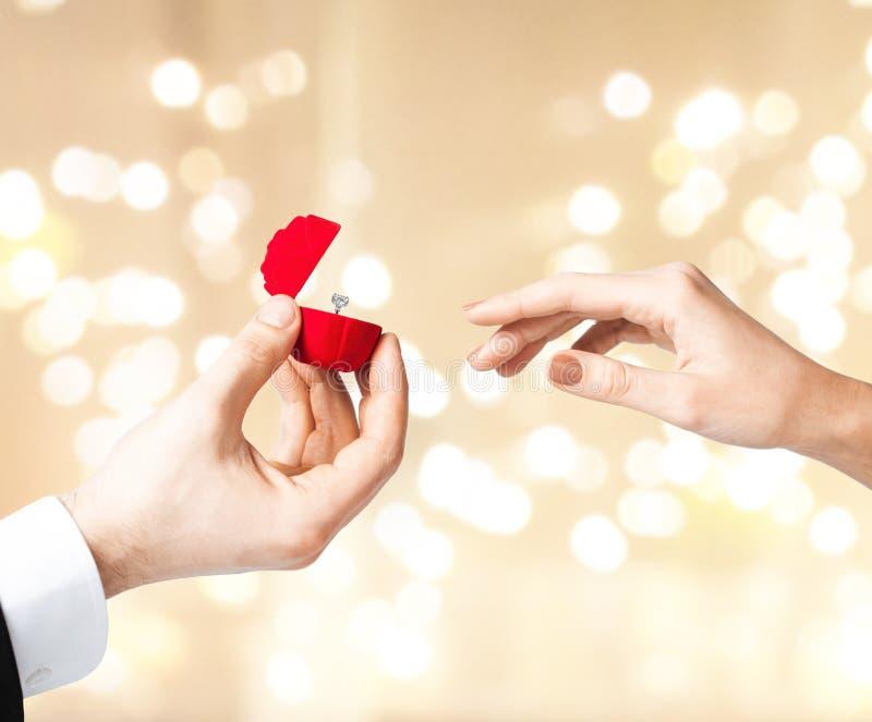 Man som ger diamantcirkeln till kvinnan på valentindag royaltyfria foton