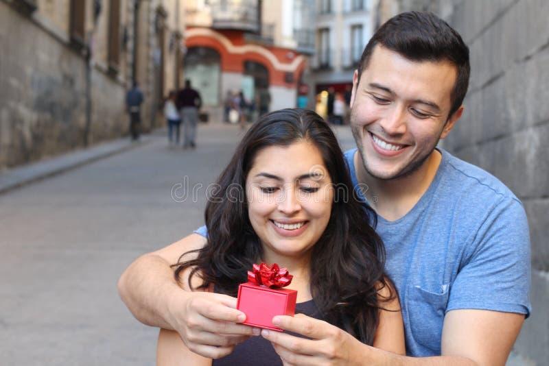 Man som ger en gåva till en ursnygg kvinna royaltyfri bild