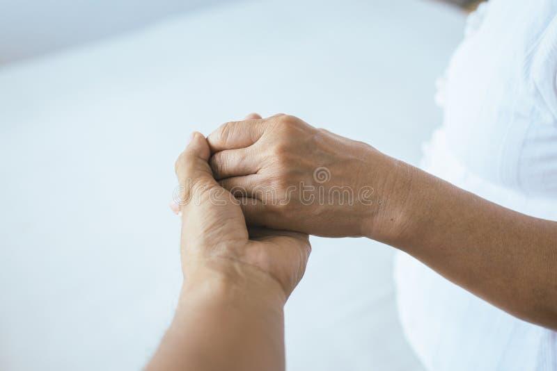 Man som ger handen till den deprimerade äldre kvinnan, psykiater som rymmer handpatienten, mentalt hälsovårdbegrepp arkivfoto