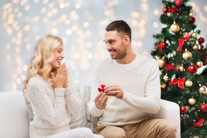 Man som ger kvinnaförlovningsringen för jul royaltyfri foto
