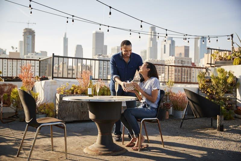 Man som ger kvinnagåvan, som de firar på takterrass med stadshorisont i bakgrund arkivfoton