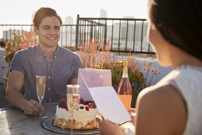 Man som ger kvinnagåvan, och kort, som de firar på takterrass med stadshorisont i bakgrund royaltyfria bilder