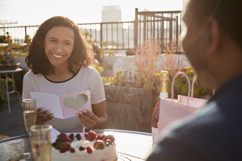 Man som ger kvinnagåvan, och kort, som de firar på takterrass med stadshorisont i bakgrund royaltyfri foto