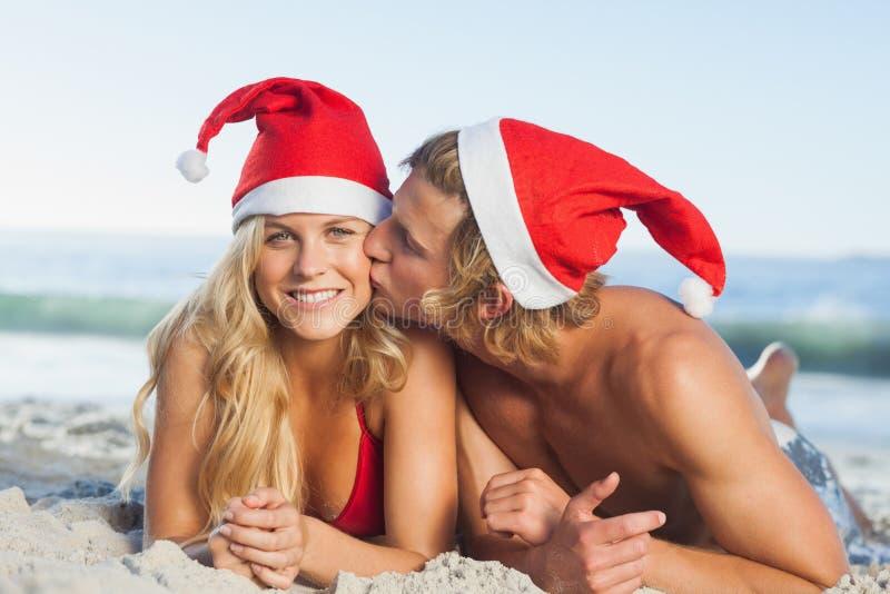 Man som ger kyssen till bärande julhattar för partner arkivbilder