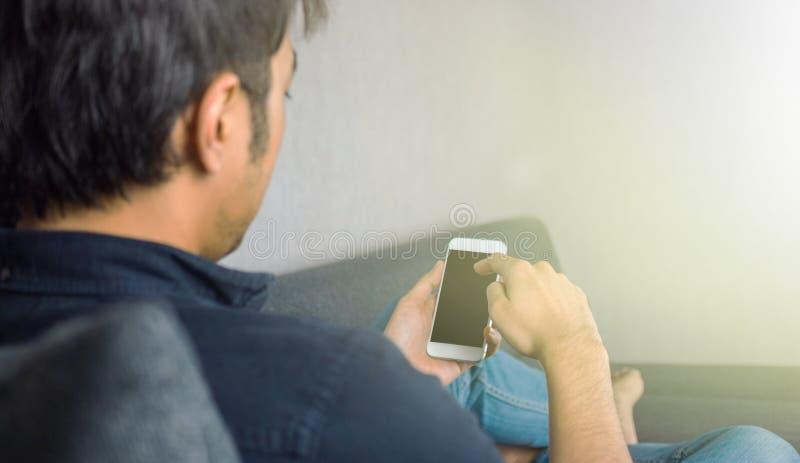 Man som glider telefonen som hemma sitter på soffan fotografering för bildbyråer