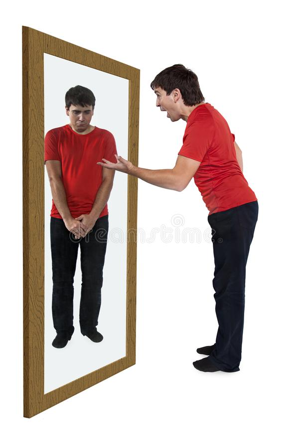 Man som grälar på sig i en spegel royaltyfria bilder