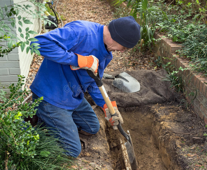 Man som gräver diket för att byta ut avklopplinjen rör och gräsmattastänk royaltyfri bild
