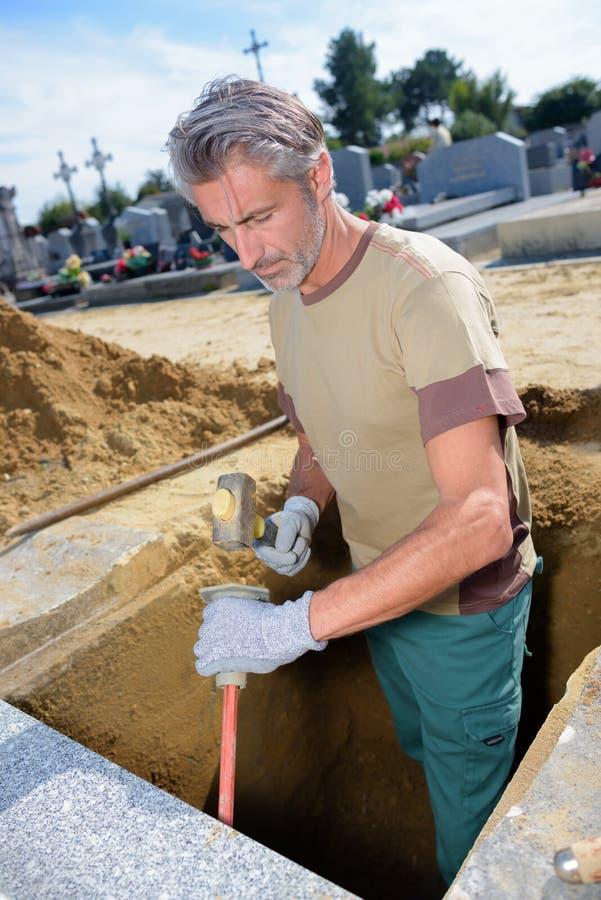Man som gräver i gravvalv arkivfoto