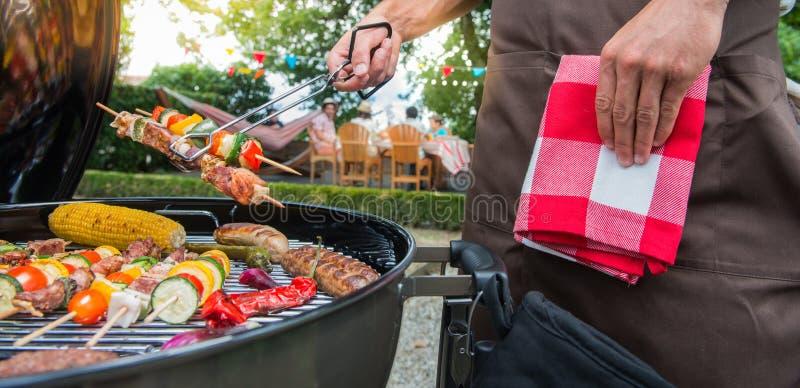 Man som grillar kött på det trädgårds- grillfestpartiet royaltyfria foton