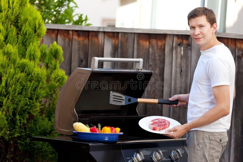 Man som grillar mat arkivfoto