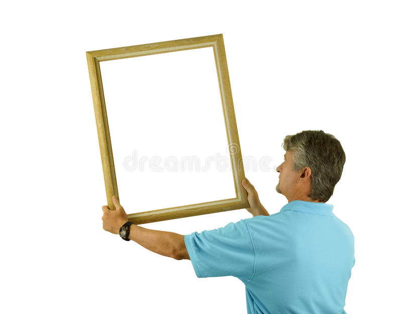 Man som hänger eller rymmer den tomma bildramen på väggen royaltyfri fotografi