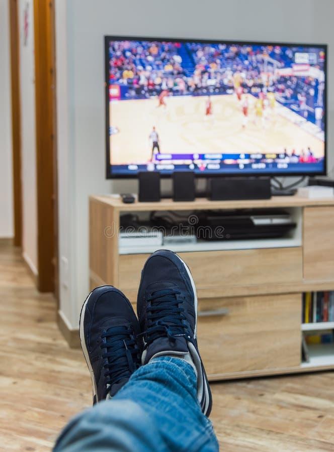 Man som håller ögonen på en basketmatch på tv royaltyfria foton