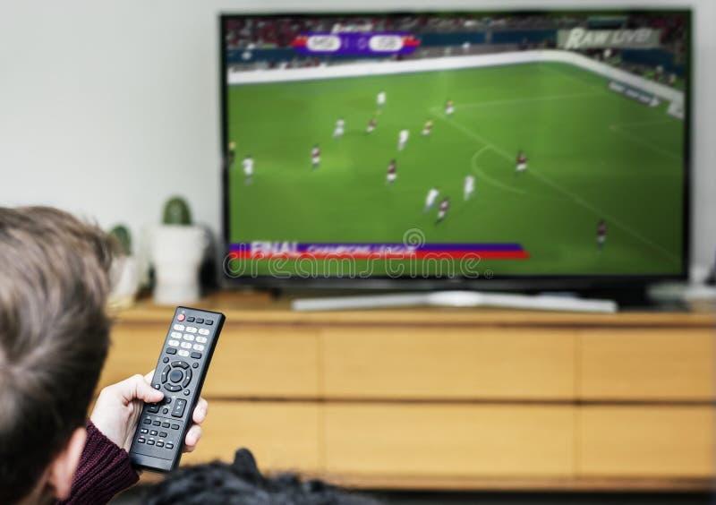Man som håller ögonen på en fotbolllek på TV arkivfoto