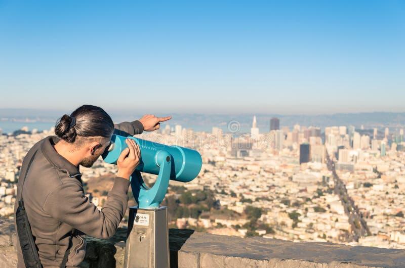 Man som håller ögonen på Francisco Downtown på ett binokulärt från tvilling- maxima royaltyfria bilder