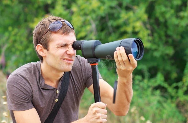 Man som håller ögonen på, i spotting av räckvidd fotografering för bildbyråer