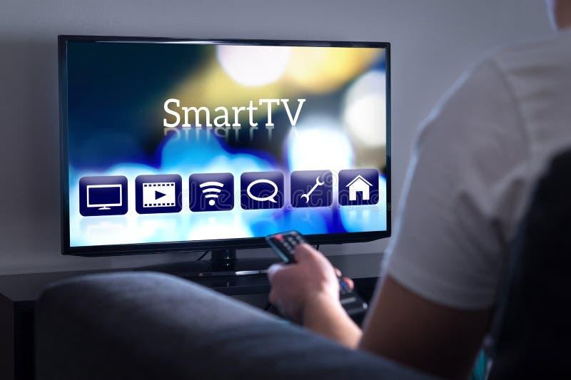 Man som håller ögonen på smart tv Välja film eller serie från menyn royaltyfri fotografi