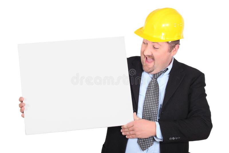 Man som ha på sig den gula hårda hatten arkivbild