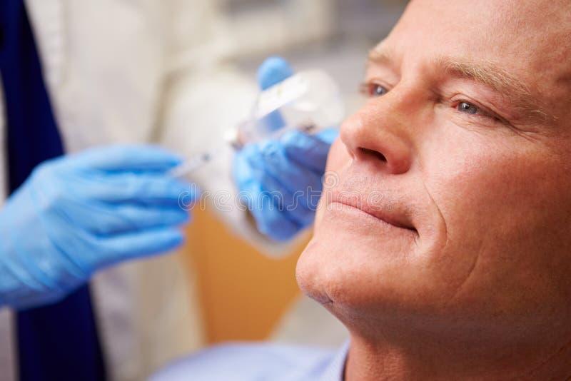 Man som har Botox behandling på skönhetkliniken arkivbilder
