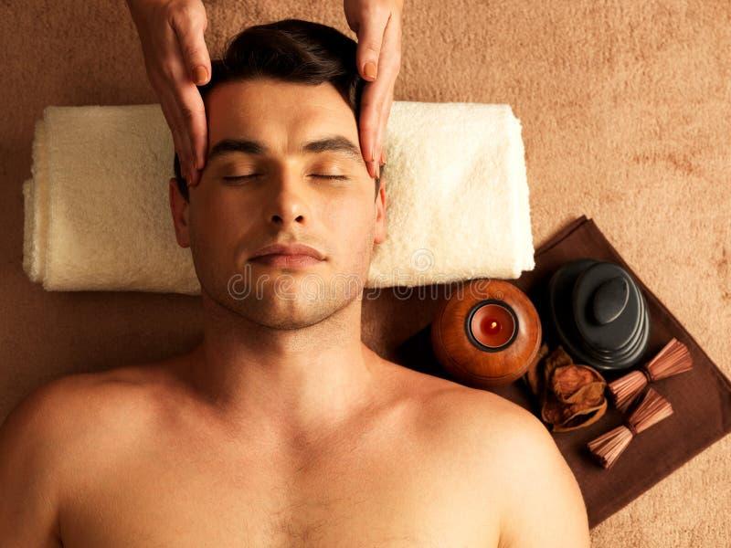 Man som har den head massagen i brunnsortsalongen royaltyfri bild