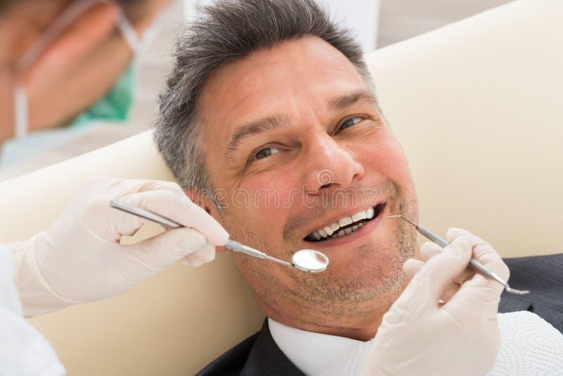 Man som har den tand- kontrollen-upp i klinik arkivfoto