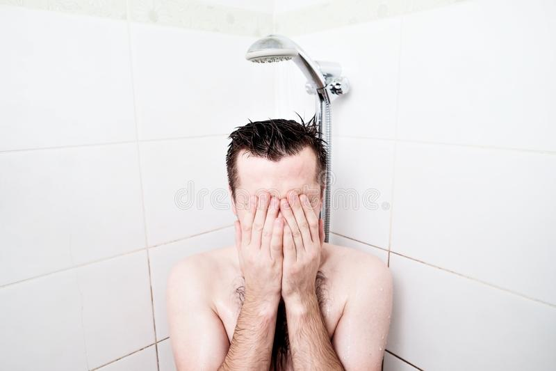 Man som har en avslappnande dusch Koppla av i duschen efter ett arbete för ` s för hård dag arkivfoto
